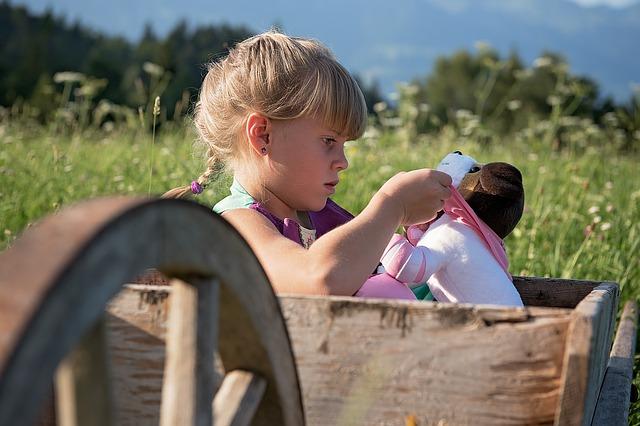 dívka sedící venku v přírodě a hrající si s panenkou